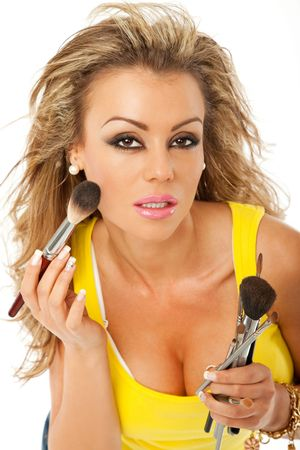 beautiful woman is applying makeup with a brush Stock Photo