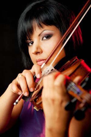 beautiful young female violinist is performing on black background Stock Photo