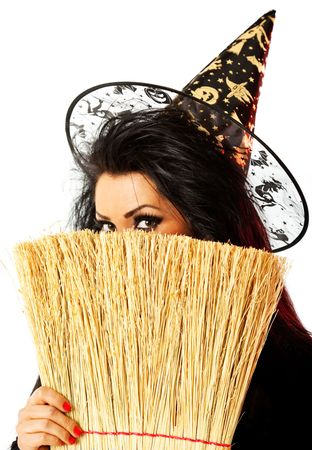 young female dressed up as a witch hiding behind broom Stock Photo