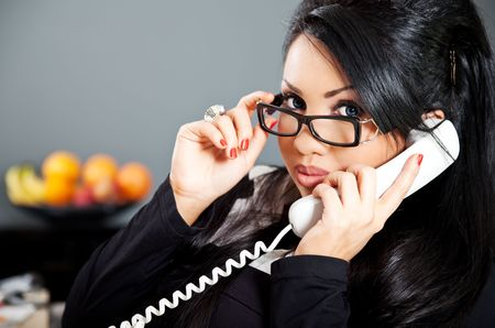 administrativo: young hispanic business person with eyeglasses on the phone Banco de Imagens