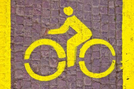 horizontal yellow bicycle line sign on the pavement  Stock Photo