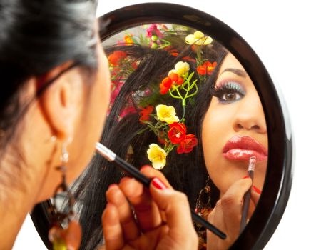 reflection in a mirror of a beautiful hispanic female applying lipstick