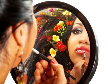 reflection in a mirror of a beautiful hispanic female applying lipstick