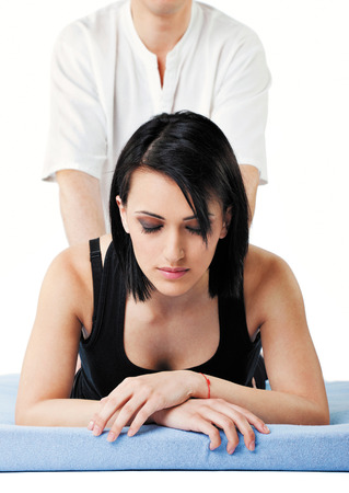 Young woman receiving lower back thai massage from a man, eyes closed Stock Photo