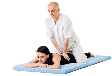 Woman lying on mat receiving massage from thai therapist, isolated on white