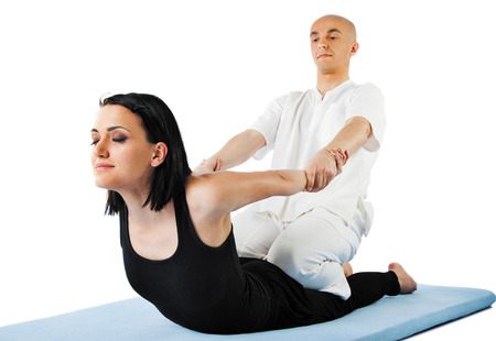 pressure massage: Young female receiving massage by therapist in traditional thai position