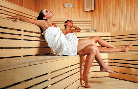 Two beautiful young females with towels relaxing at sauna Stock Photo