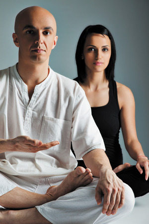 Man in white and woman in black doing yoga exercise, meditation