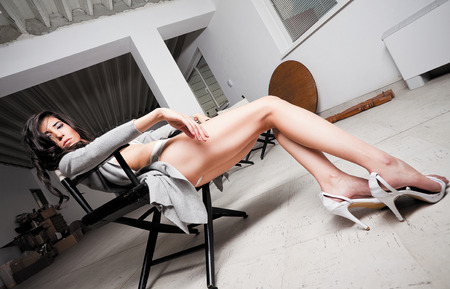 fatigued: Beautiful female model leaning on a chair backstage, looking tired