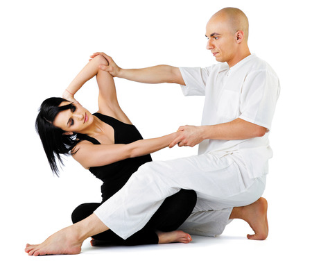 Young female sitting and receiving traditional thai arm stretching massage by therapist, isolated on white