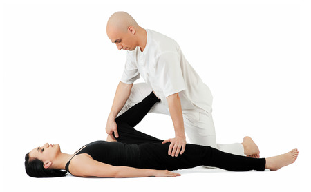 Young female lying and receiving traditional thai massage by therapist on her legs