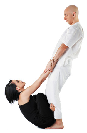 Young woman in traditional thai position with legs crossed, being stretched by therapist Stock Photo