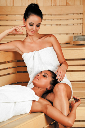 Two beautiful females relaxing at sauna, one lying in  others lap Stock Photo