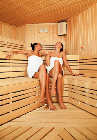 Two beautiful females with towels relaxing at sauna chatting and laughing
