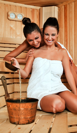 Two beautiful happy females in sauna, hugging and laughung