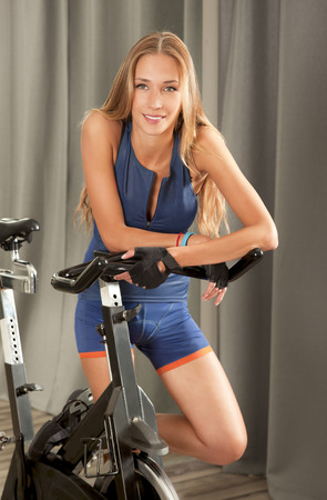 Beautiful young woman in sports outfit standing next to a spin bicycle in a jim. Stock Photo