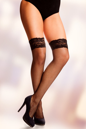 work path: Beautiful long crossed woman legs in black mesh stockings, isolated with work path. Stock Photo