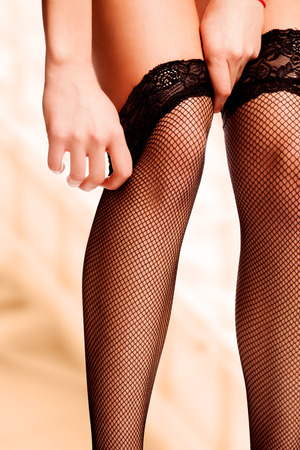 work path: Work path isolated womans hands reaching to pull up the mesh black stockings on her beautiful legs.