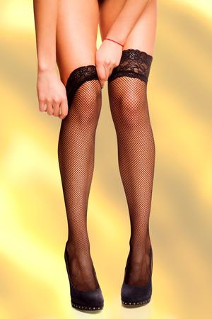 pull up: Percorso del lavoro isolato womans mani che raggiungono per tirare su la maglia calze nere sulle sue belle gambe in alta collina. Archivio Fotografico