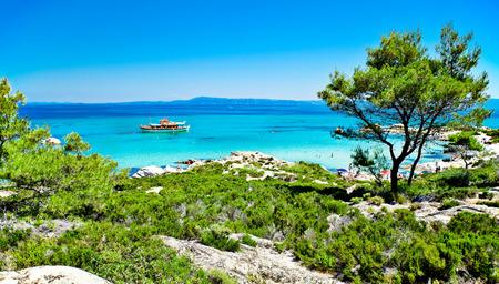 A panoramic view of Portokali (Orange) Beach  in Sithonia, Halkidiki, Greece with a tourist ship. Its original name is Kavourotripes.
