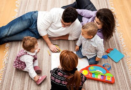 padres hablando con hijos: grupo familiar de cinco en el suelo - dos bebés y tres adultos en el medio de una conversación.