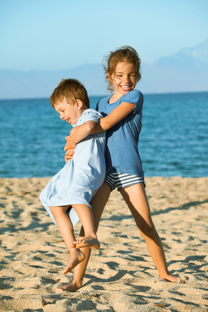 Two kids - seven and three on the beach playing. Sister is lifting and spinning arround her younger brother laughing.