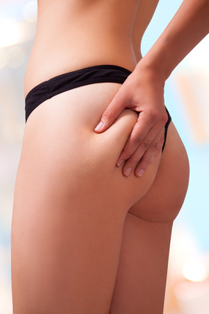 grabbing back: Woman is holding a bit of fats on her butt. Image isolated with work path.