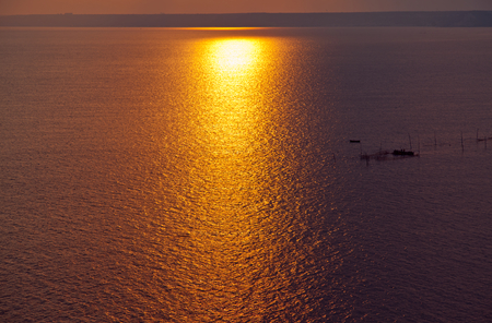 yewoll sunset or sunrise over a wide body of water - ocean , sea or lake. Stock Photo