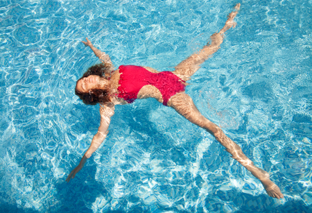 laying on back: Beautiful young woman laying back on water in pool, star position - relaxed under the sun.