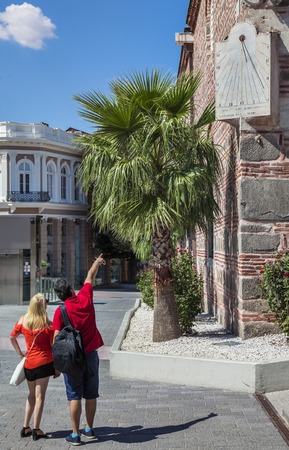 Couple tourists looking at sun clock on the corner of Dzhuaya, Djumaya Mosque or Cuma Camii in turkish, downtown Plovdiv on a sunny summer day. Stock Photo