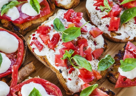 Creamy cheese over crispy toasts topped with tomatoes and basil. Horizontal image.