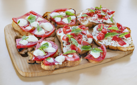 souse: Creamy cheese over crispy toasts topped with tomatoes and basil. Horizontal image.