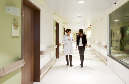 Doctor explaining something to a patient while walking through a hospital corridor.