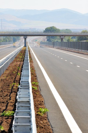 A vertical, image of an empty highway road and an overpass above it. Stock Photo