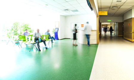 corridors: View of the registration desk, waiting area and a corridor in modern hospital with blurred figures of patients and a copy space.