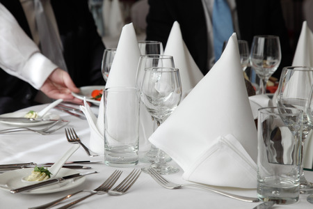 Close-up of the hand of a waiter, serving on elegantly set table with two dressed-up persons.
