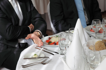 Close-up of the hand of businessman, attempting a business meeting in a fancy restaurant on a elegantly set table.