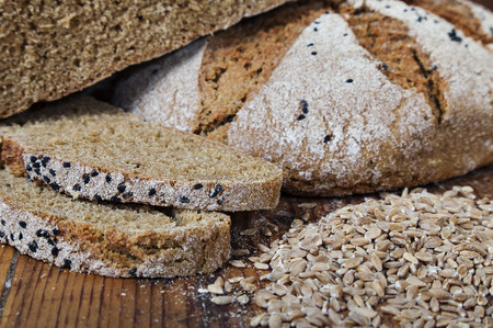 Horizontal image of couple slices of full grain bread with some pile of wheat grains and a whole bread in the background.