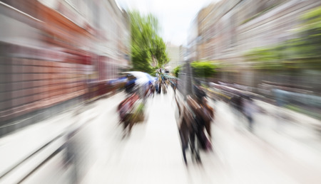 A horizontal image, motion zoom blurred picture of a pedestrian walk street in a city downtown. Stock Photo