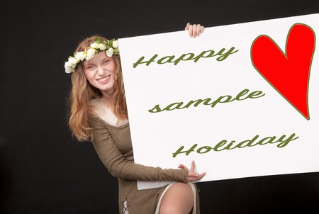 A playful beautiful woman with white roses wreath in her long hair is holding and showing a sign with red heart, sample text and a clipping path. Stock Photo