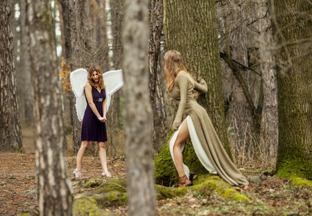 Two beautiful women in a fairytale forest. One as fairy with wings , the other is looking at her through the trees. Stock Photo