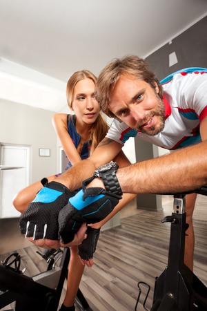 A young male and a female on cycles in a gym, looking at the camera.