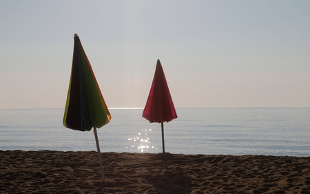 Two folded sun umbrellas on an empty beach by the sea early in the morning. Stock Photo