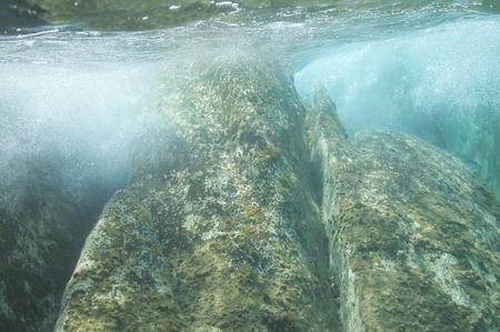 Underwater image of waves, crashed in the seashore rocks.