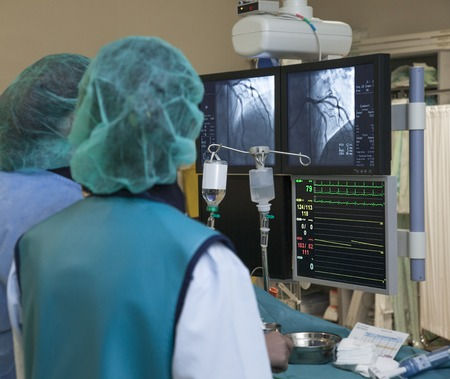 Monitors with scanner image of heart arteries and heartbeat during non-invasive surgery in hospital. Stock Photo