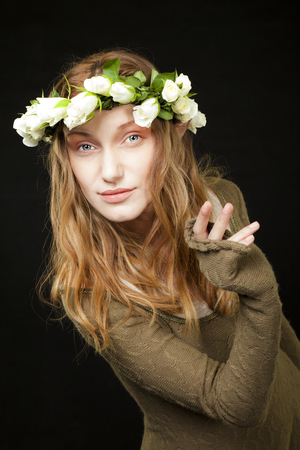 A smiling beautiful woman with white roses wreath in her long hair is holding or peeking behind nothing.
