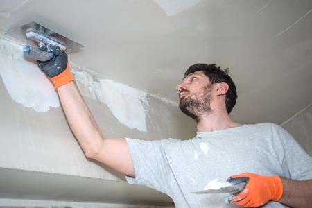 Worker Plastering Ceiling