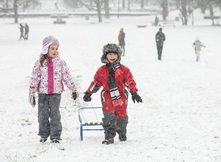 Two Happy Kids Snow Sled Banco de Imagens