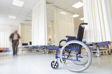 A wheelchair in modern hospital with empty beds and a blurred patients figure.