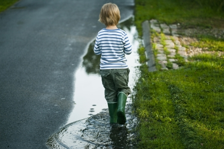 splash back: A Boy with Green rubber boots is walking through a puddle.